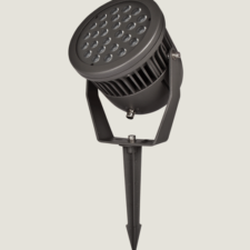 A black outdoor spotlight with an spike accessory on a grey background.