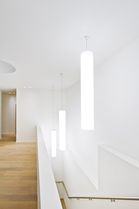 A modern staircase with large white round pendant lights.