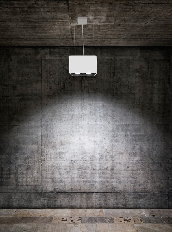 A white suspended box pendant light on a concrete wall at a gallery.