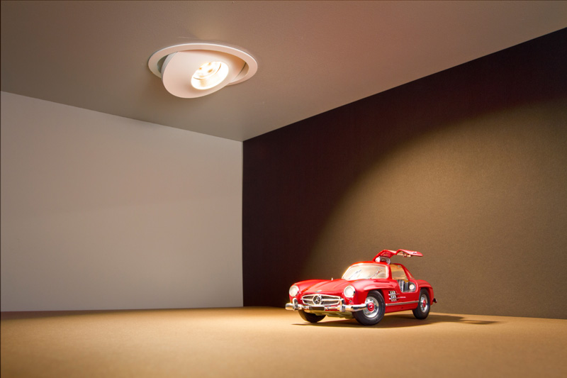 A miniature red car focused by a flat led downlight