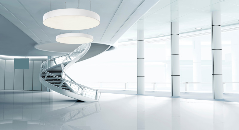 A stylish white office space with a spiral staircase and 2 large round pendant lights.