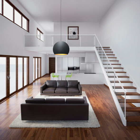 A modern living room with 2 sofas, a staircase and a black pendant light.