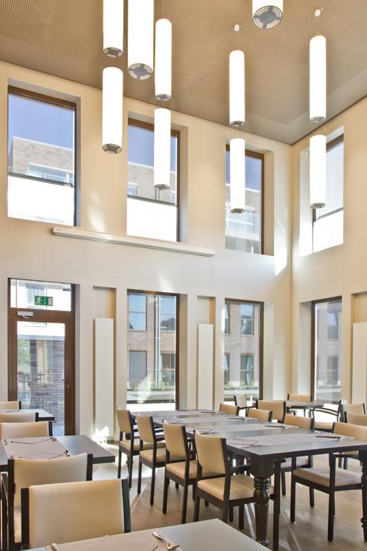 A modern restaurant full of windows and round pendant lights.