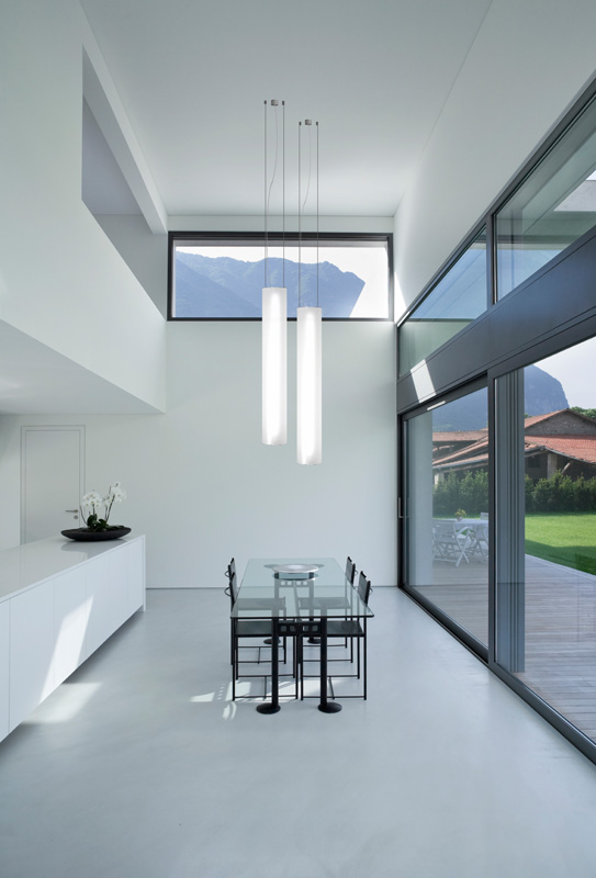 A modern dinning room with white round pendant lights.