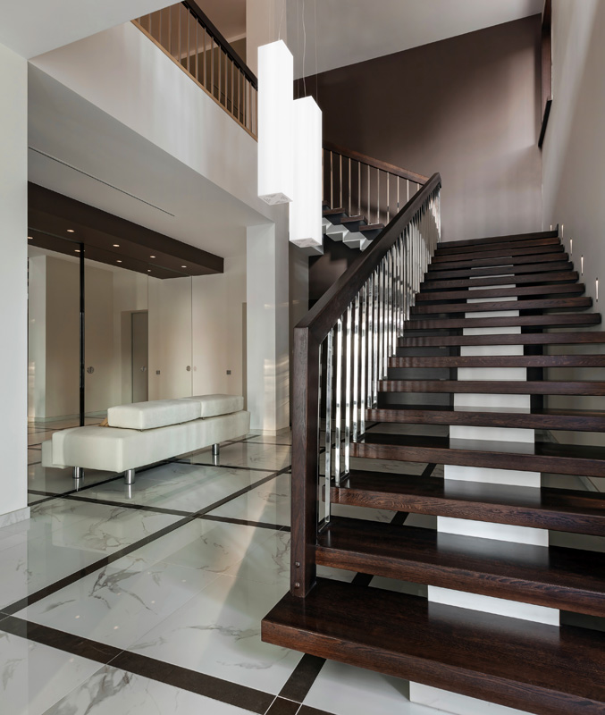 Luxury hall with staircase of a modern house with two large pendant lights.